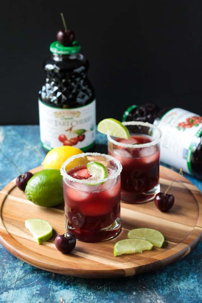 Two glasses of Tart Cherry Sparkling Lemonade on a round wooden platter. Fresh lime slices and fresh cherries on the platter too.