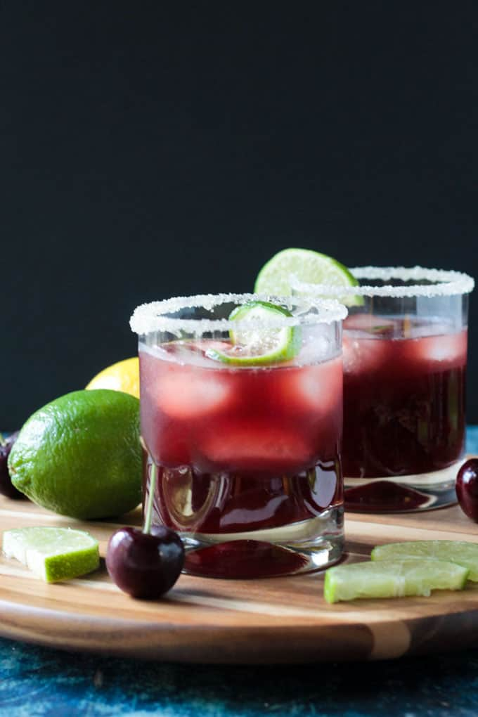 Two glasses of Tart Cherry Sparkling Lemonade garnished with sugar on the rims and lime slices. Fresh cherries and lime slices on the table by the glasses.