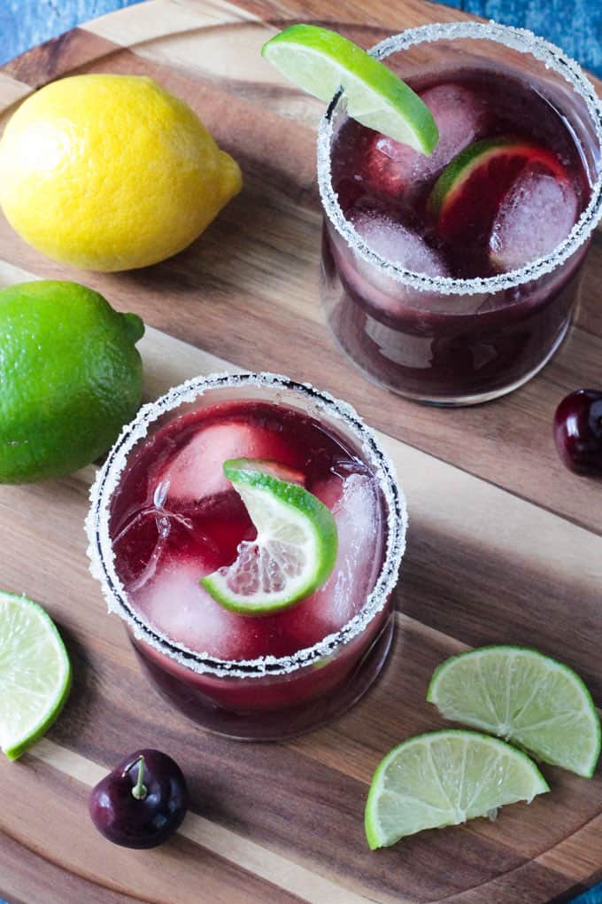 Overhead view of a glass of Tart Cherry Sparkling Lemonade with ice and a twisted slice of lime.