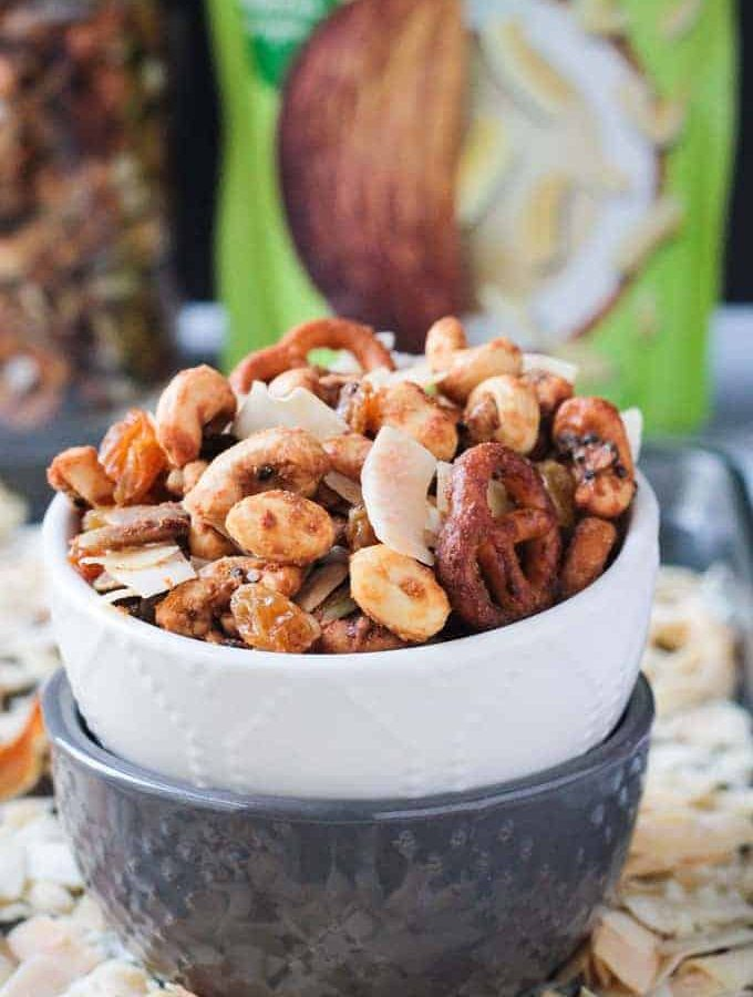 Close up front view of homemade trail mix in a white bowl stacked on top of a gray bowl.