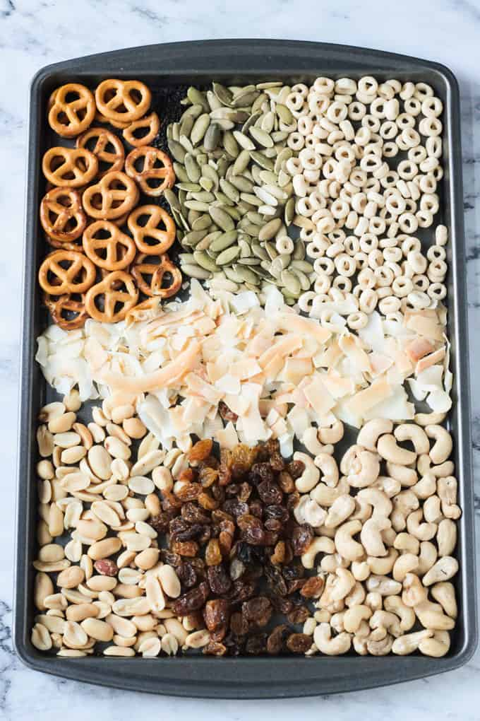 Baking tray with trail mix ingredients lined up - pretzels, pumpkin seeds, cheerios, coconut flakes, peanuts, golden raisins, and cashews.