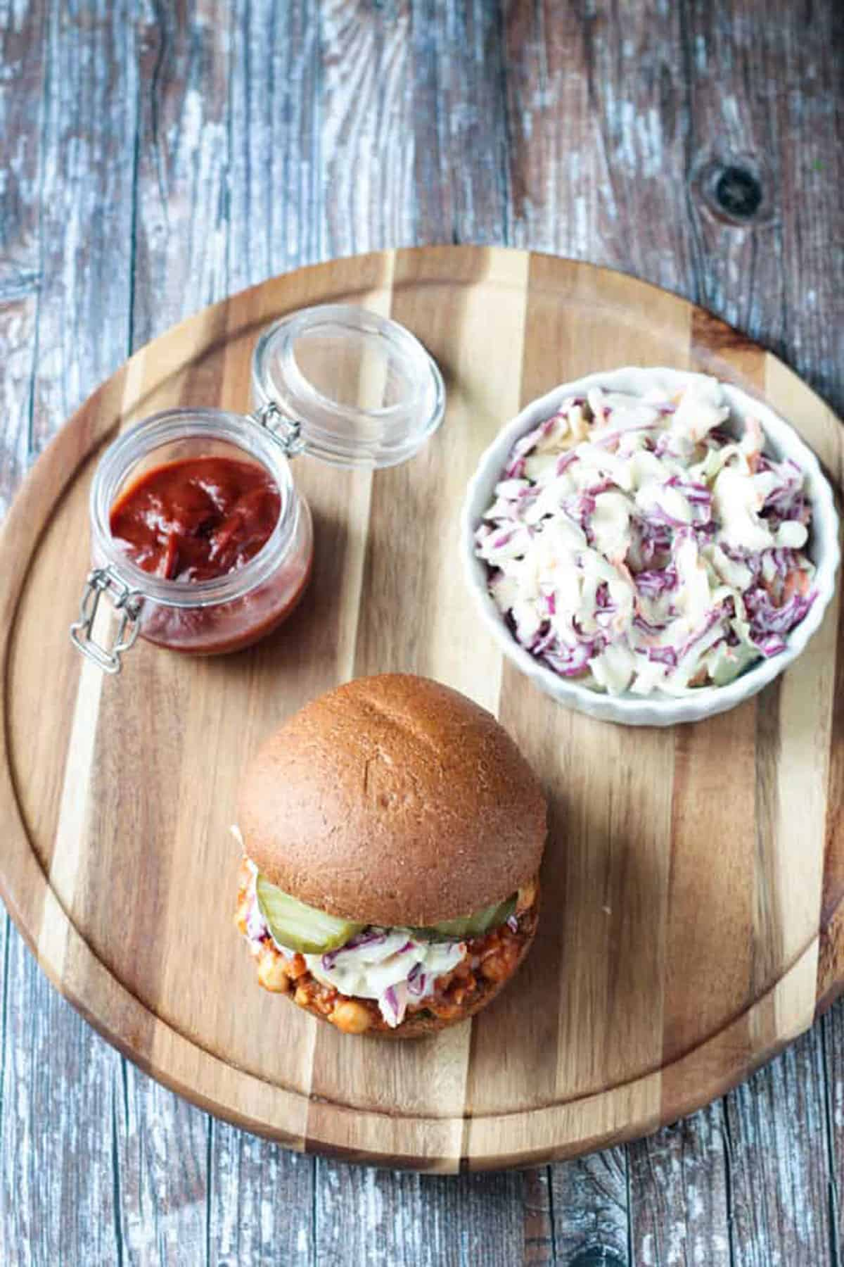 Overhead view of a bbq sandwich, bowl of coleslaw, and a jar of sauce.