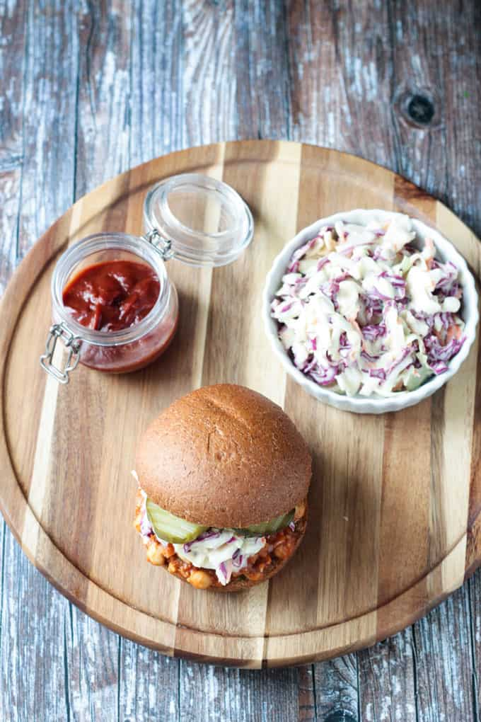 Overhead view of a round wooden platter holding a chickpea bbq sandwich, small bowl of coleslaw, and a small jar of bbq sauce.