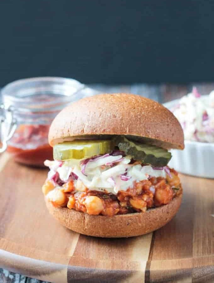 Vegan Chickpea BBQ Sandwich topped with creamy dairy free coleslaw and pickles on a whole wheat bun.