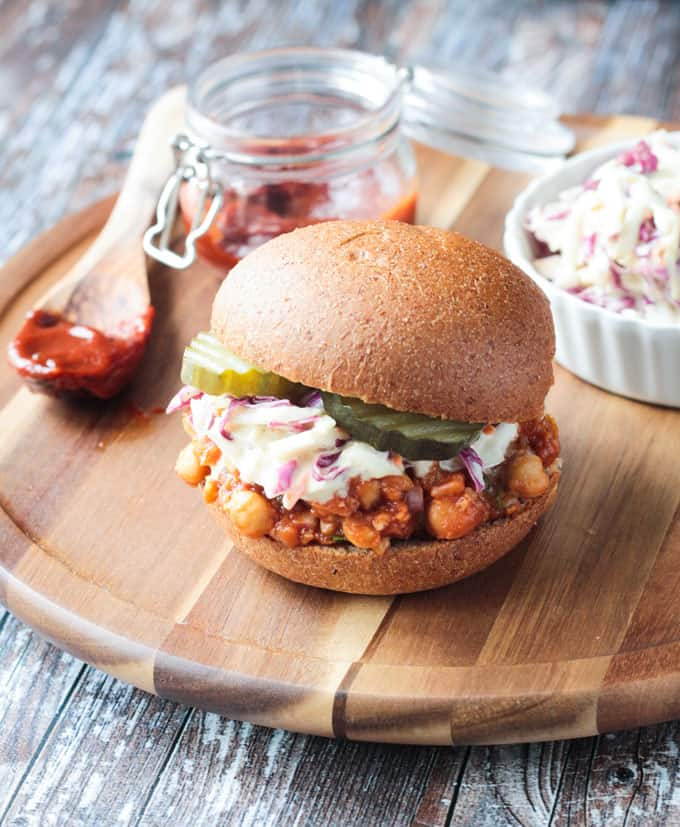 Vegan BBQ Sandwich on a round wooden platter with small jar of bbq sauce behind.