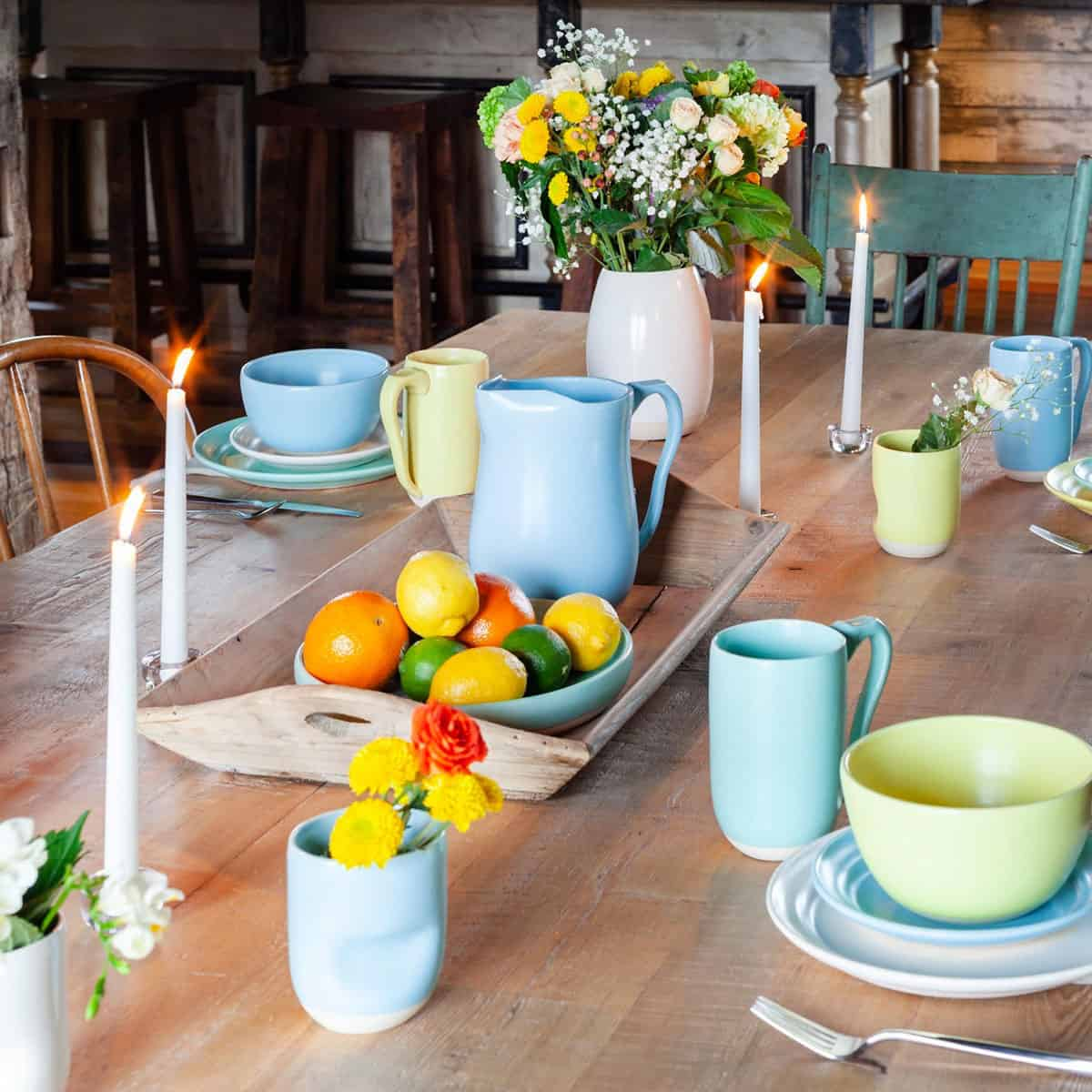 Tablescape of handmade clay dishware on a wooden farm table.