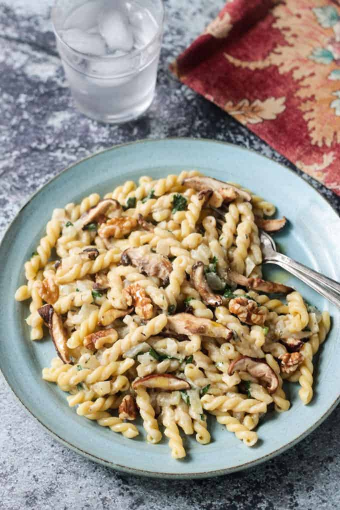 Creamy vegan mushroom pasta recipe on a blue pottery plate topped with toasted walnuts.