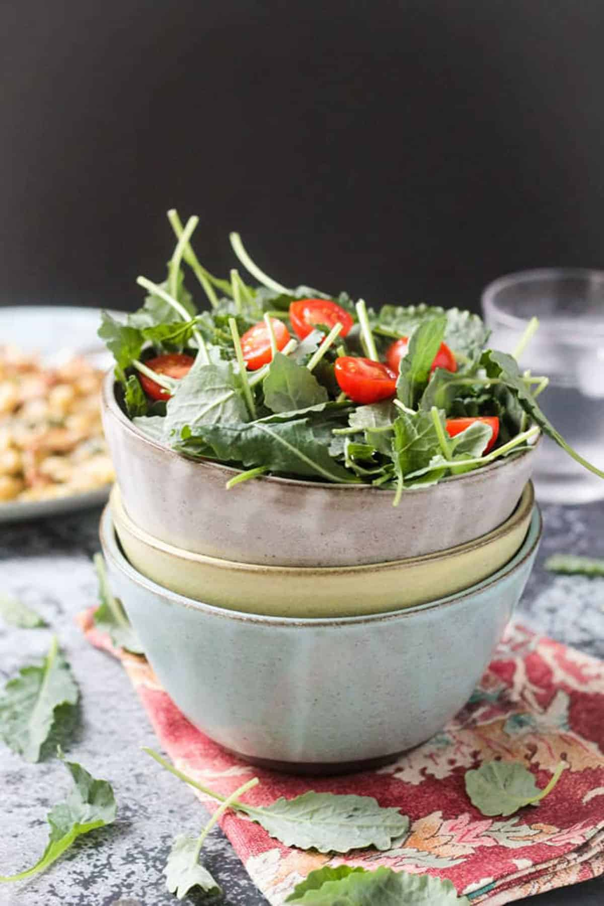 Stack of 3 bowls with baby kale and halved tomatoes in the top bowl