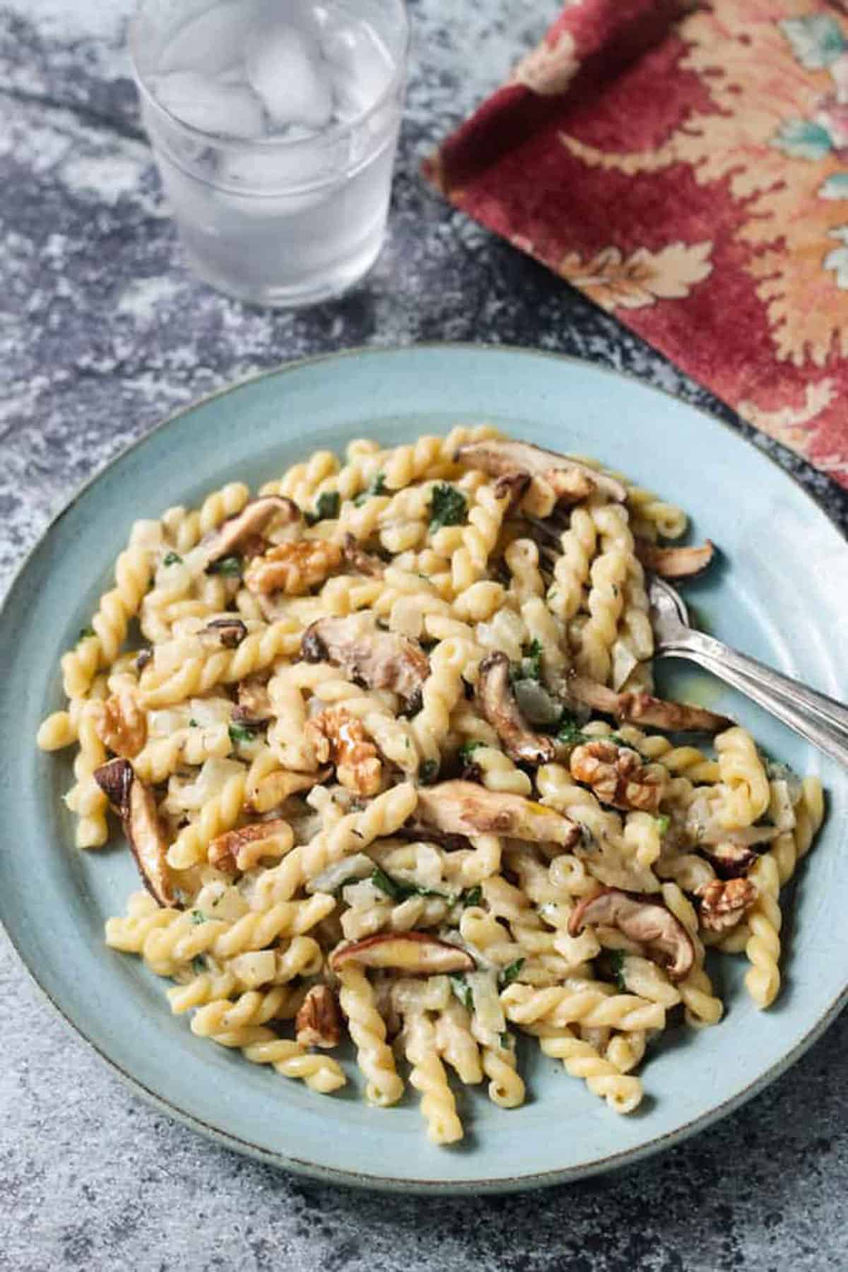 Gemelli pasta with mushrooms and walnuts on a blue plate with two forks.