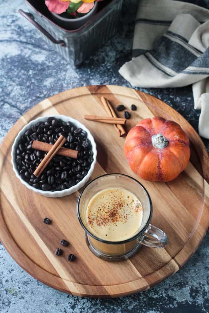 Overhead view of a Oat Pumpkin Latte on a round wooden board with a bowl of coffee beans topped with cinnamon sticks and a small decorative orange pumpkin next to them.
