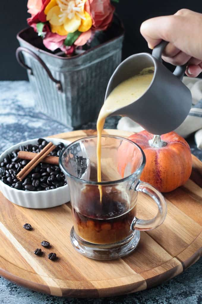 Pumpkin oat milk being poured from a small gray pitcher into a glass of coffee.