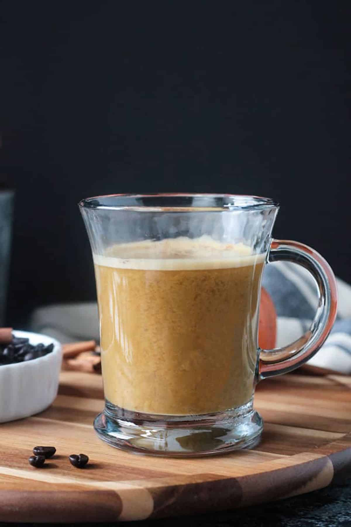 Pumpkin Latte in a clear glass with a handle.