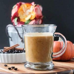 Front view of a glass of Pumpkin Latte. Orange decorative pumpkin and a small metal bucket of flowers in the background.