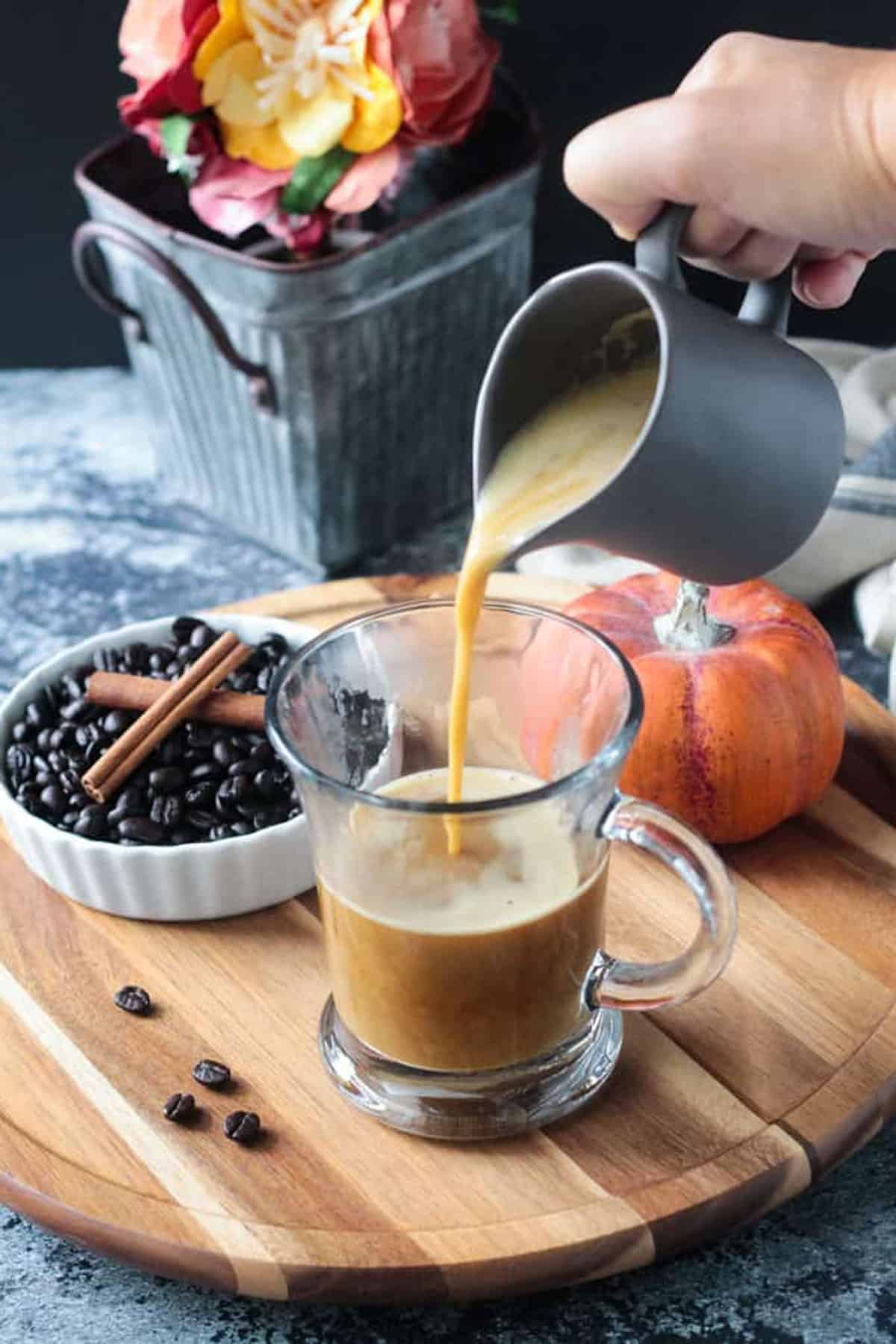 Latte being made by pouring the pumpkin milk into a glass of coffee.