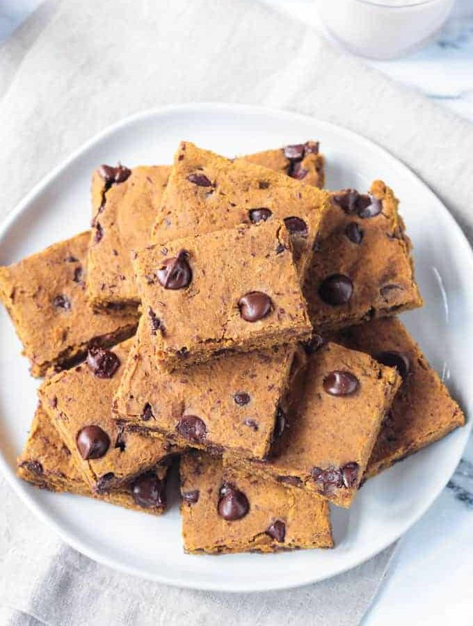 Overhead view of a pile of pumpkin chocolate chip bars on a plate.