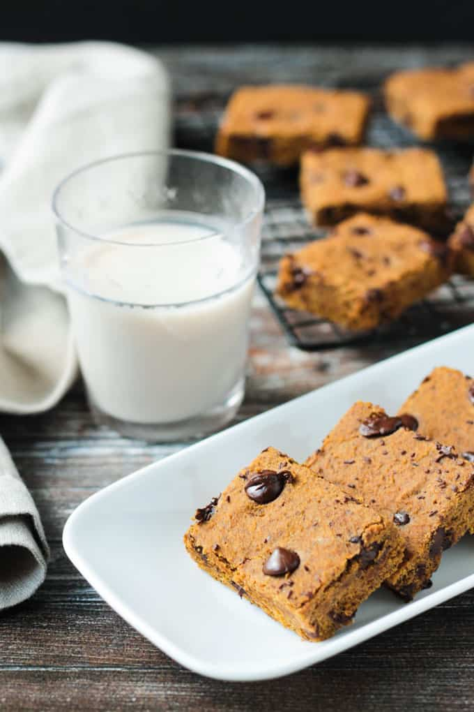 Tray of pumpkin chocolate chip bars in front of a glass of milk. Cooling rack with more bars behind.