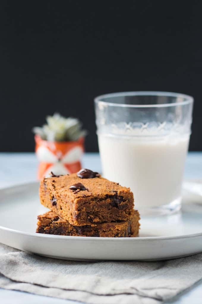 Two pumpkin chocolate chip bars stacked on a plate with a glass of milk.
