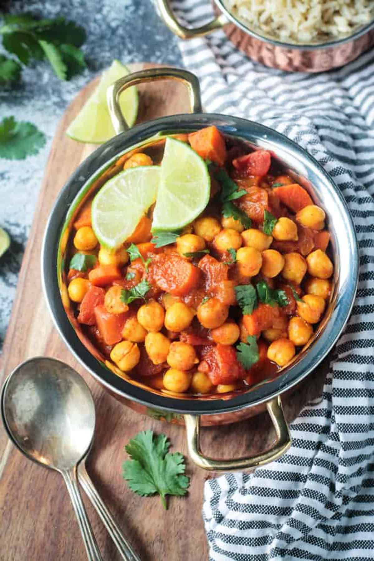 Up close overhead view of a pot of spiced chickpeas, carrots and tomatoes.