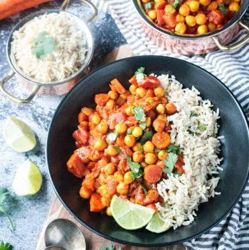 Chunky chickpea vegetable stew next to white rice in a black bowl.