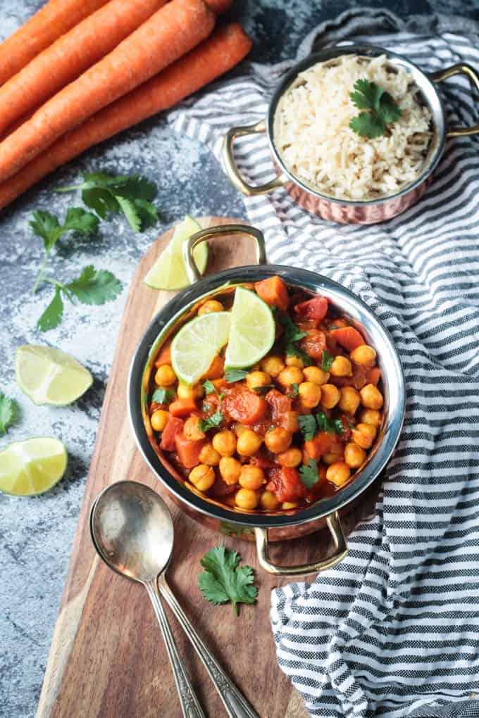 Pot of chickpea stew with two lime wedges on a wooden board. Bowl of rice behind on a striped dish cloth.