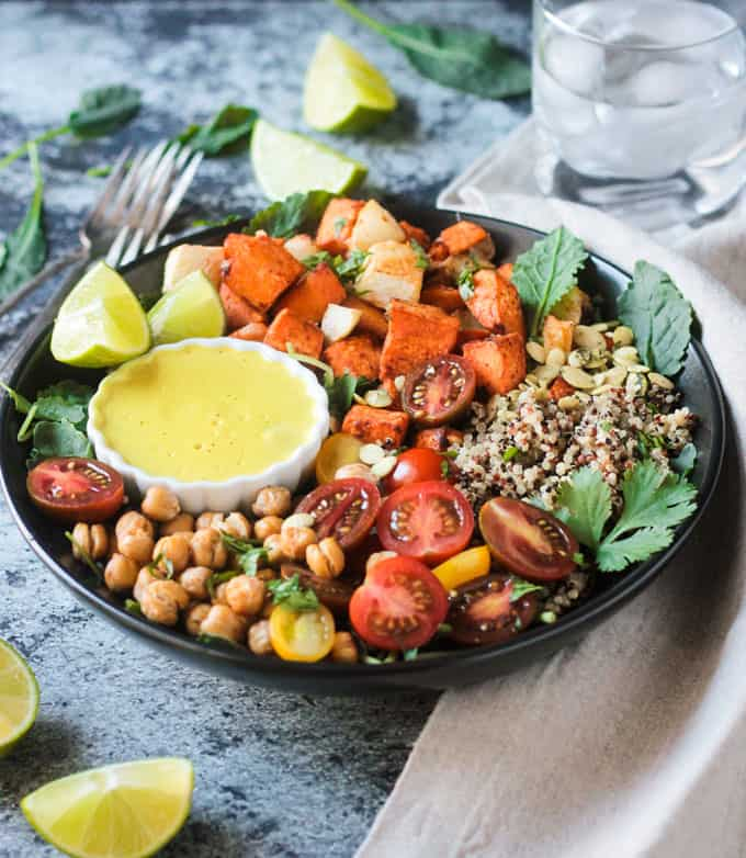 Small white bowl of cashew curry sauce in a larger black bowl full of quinoa and vegetables.