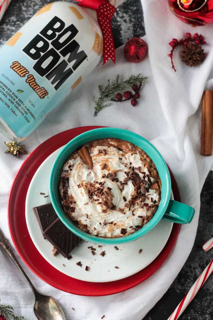 Bottle of Bom Bom lies near a mug of spiked hot cocoa topped with whipped cream, chocolate shavings, ground cinnamon and a cinnamon stick. Blue mug is on a white plate with two dark chocolate squares.