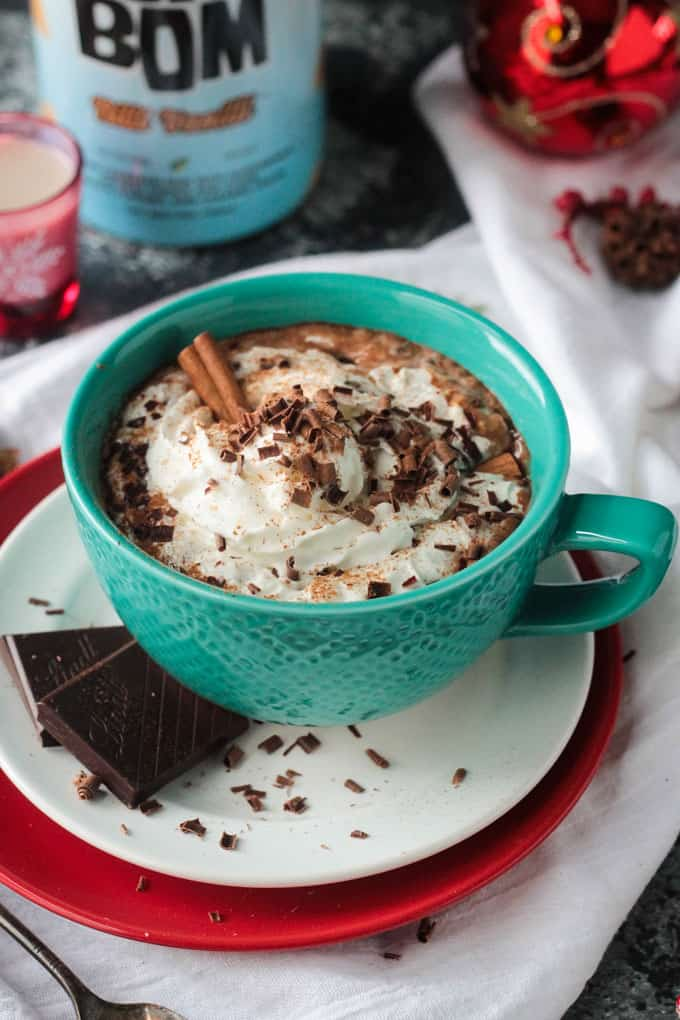 Spiked hot cocoa in a blue mug topping with whipped cream, chocolate shavings, and a cinnamon stick.