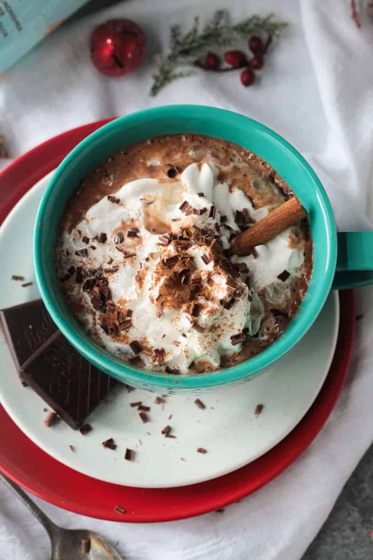 Hot cocoa topped with whipped cream, chocolate shavings, ground cinnamon and a cinnamon stick.