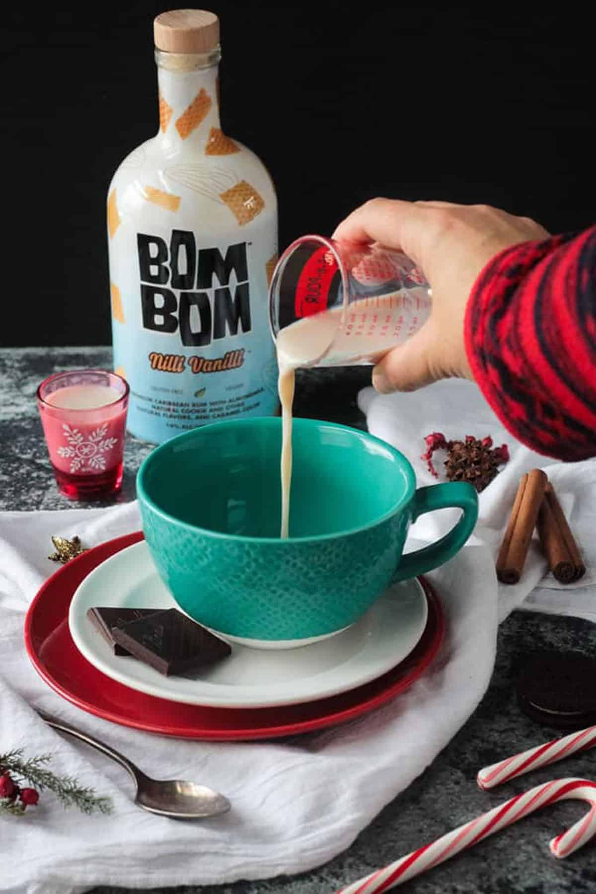 Hand pouring a shot of almond milk rum liquor into a blue mug.