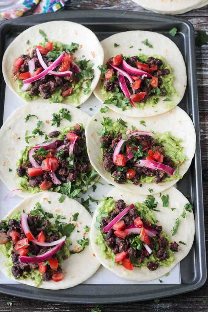 6 tortillas laid out flat on a baking sheet with black beans, guacamole, pickled red onions, and cilantro.