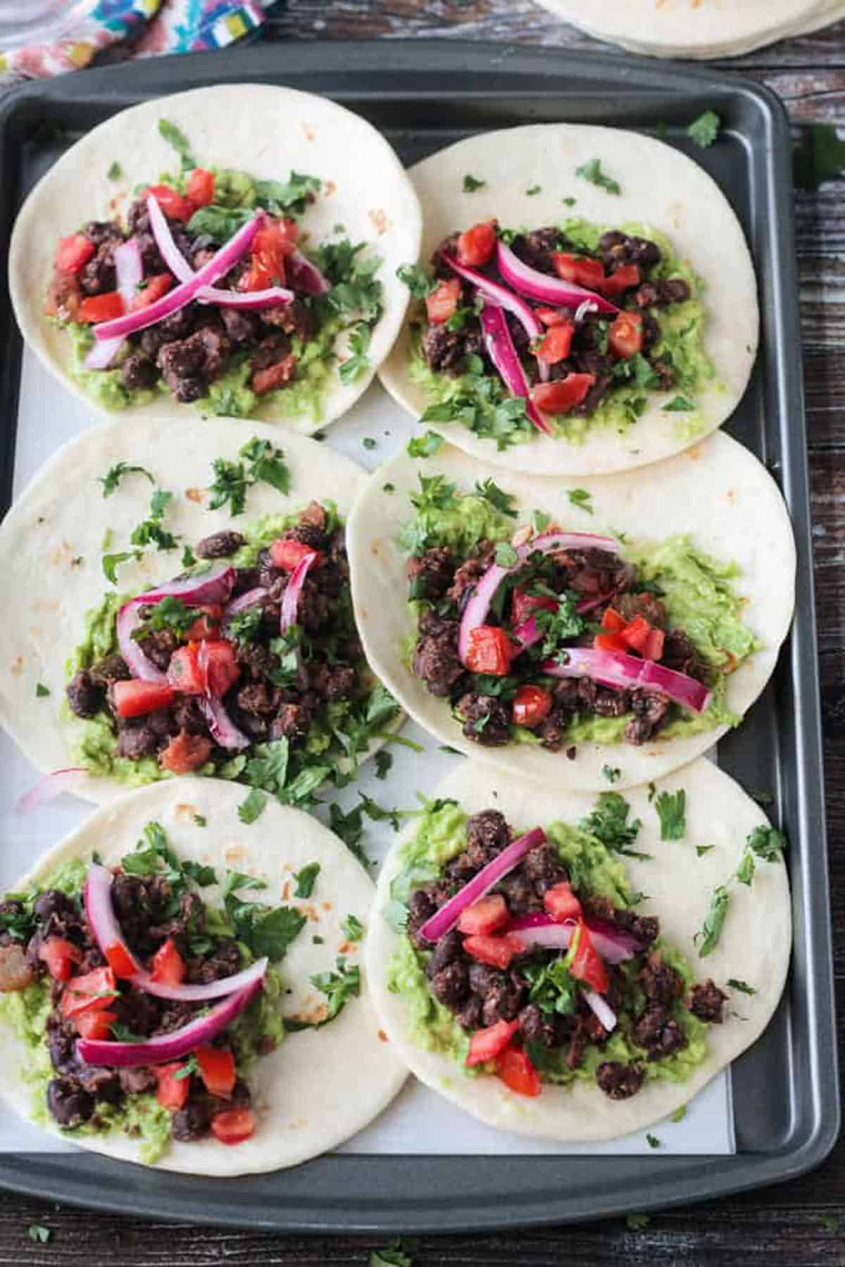 6 tortillas laid out flat with black beans, guacamole, pickled red onions, and cilantro.