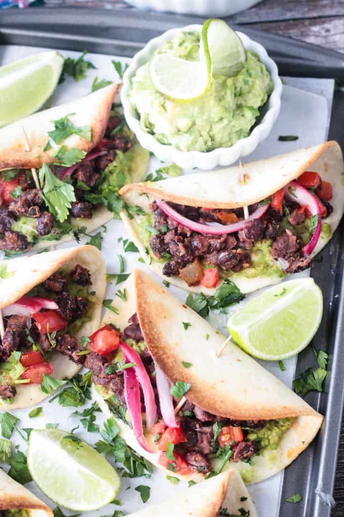 Close up overhead view of a baked mini taco with black beans, avocado, pickled red onions, and diced tomato.