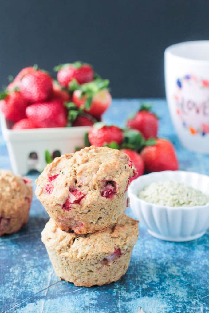 Stack of two strawberry protein muffins on a blue surface in front of a bowl full of fresh strawberries.
