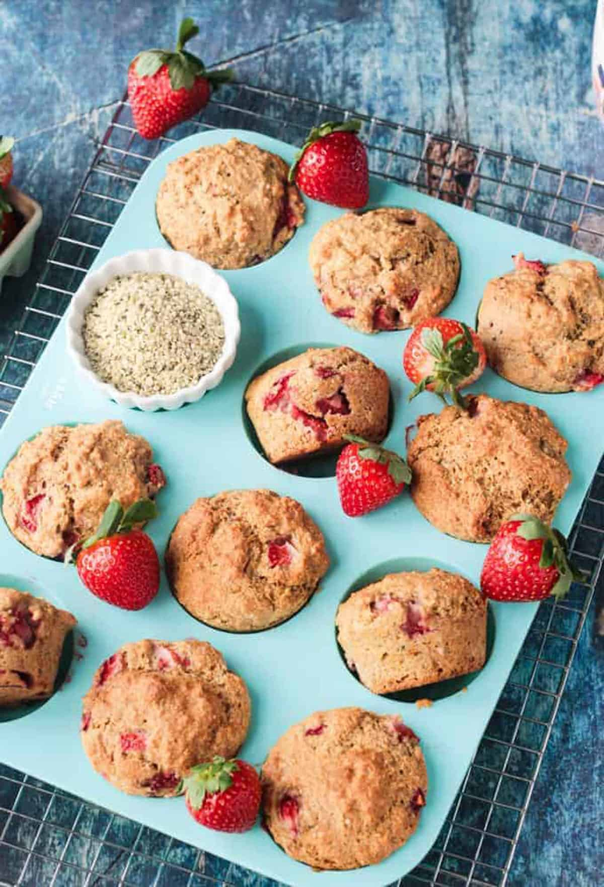 Protein muffins with strawberries in a blue silicone muffin pan.