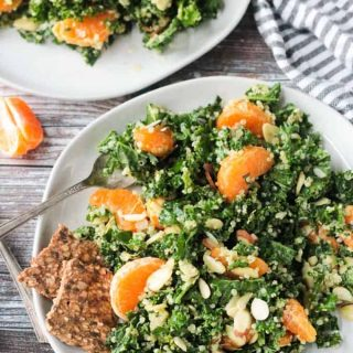 Kale and quinoa salad with orange segments and slivered almonds. Two seed and grain crackers on the side.