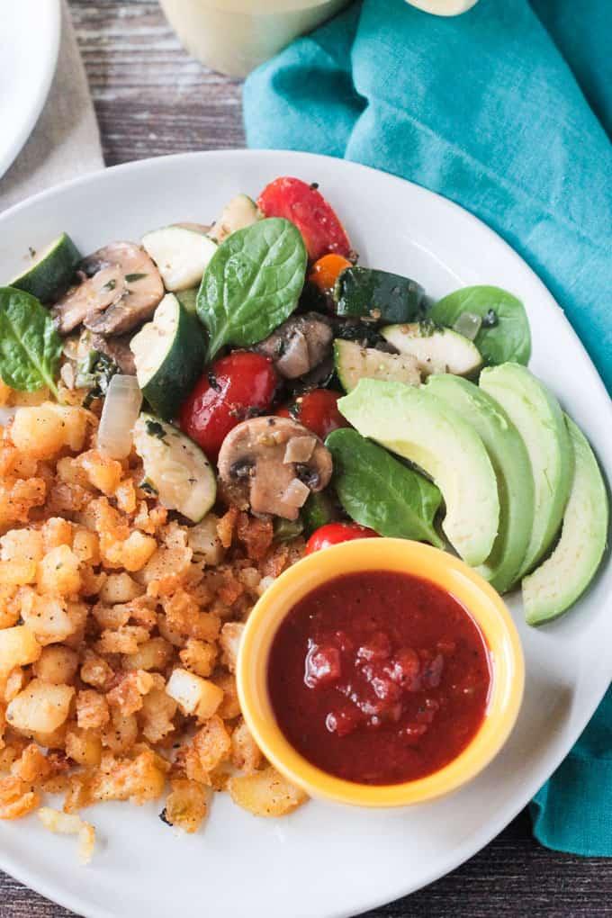 Breakfast hash browns, skillet veggies, avocado, and salsa.