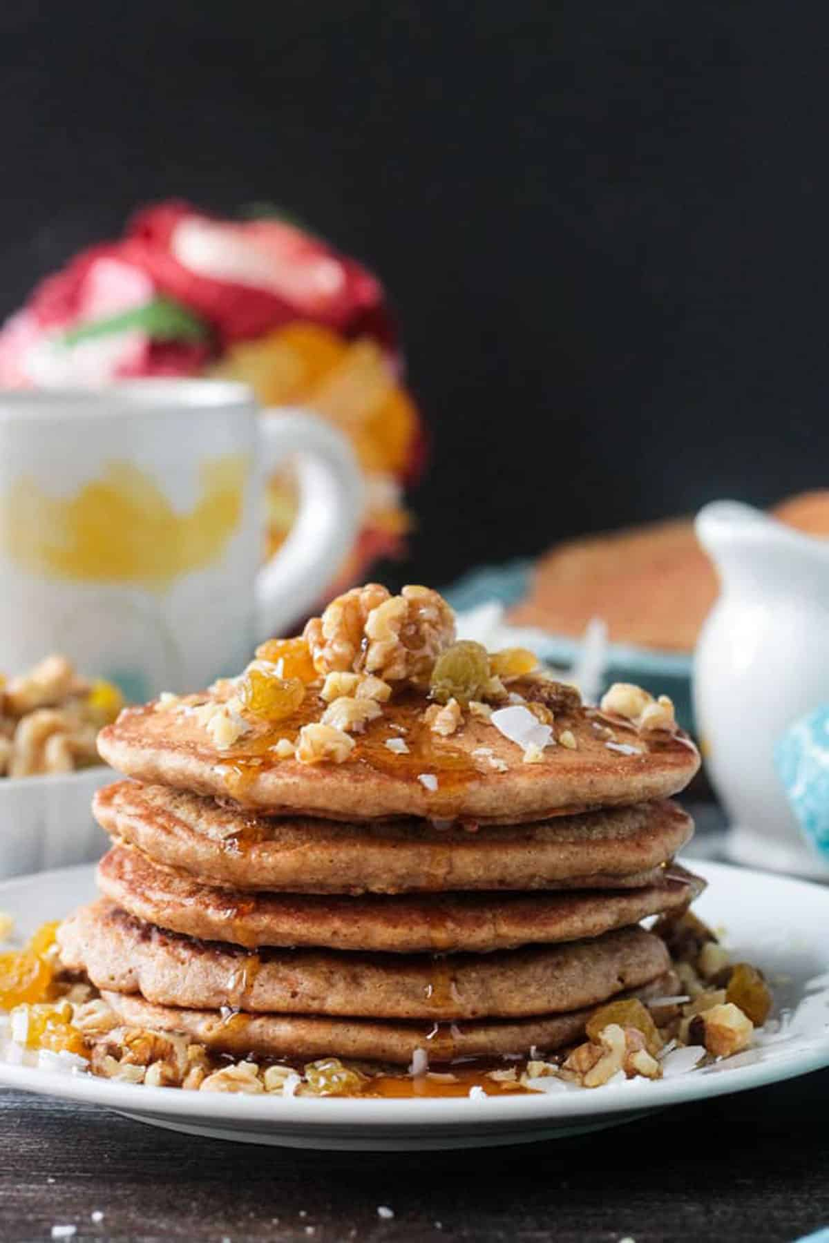 Close up of maple syrup drizzling down the side of a stack of carrot cake pancakes.