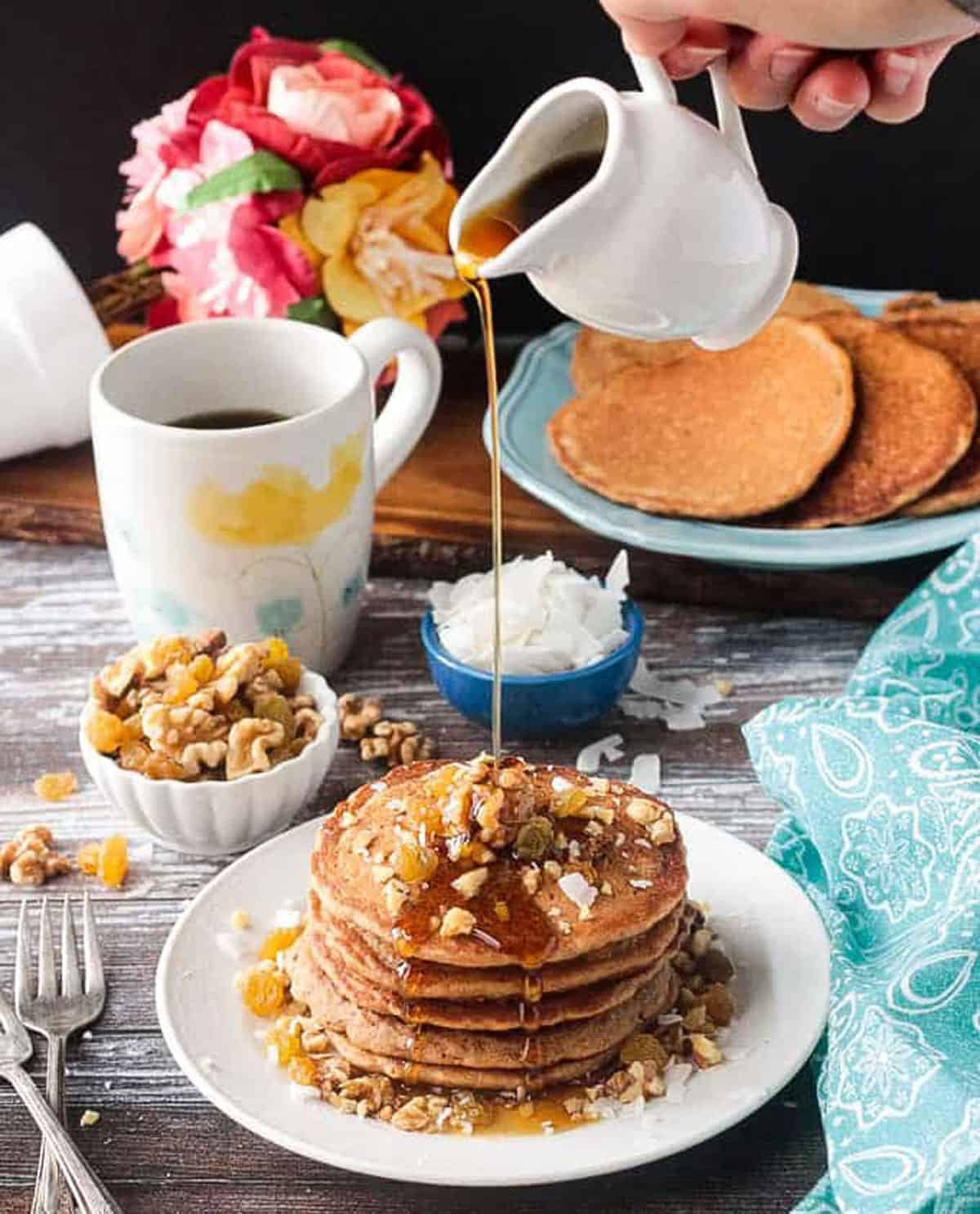Syrup being poured onto a stack of pancakes from a small white pitcher.