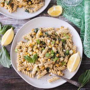 Plate of creamy sweet corn pasta topped with basil leaves.