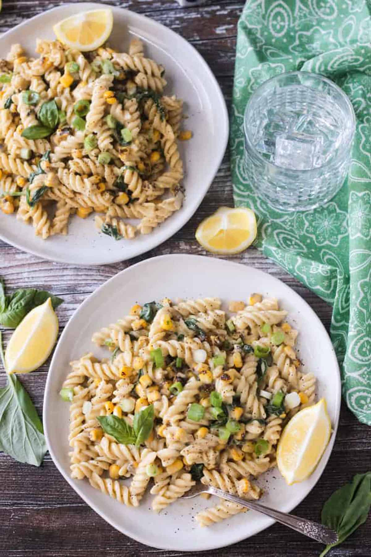 Two plates of rotini pasta with corn kernels and basil.