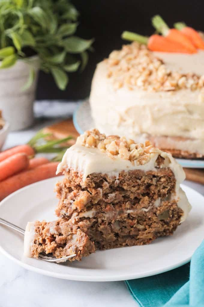 A bite of carrot cake on a fork in front of a slice of cake.