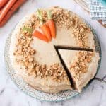 Overhead view of a carrot cake with a slice being taken out with a cake spatula.