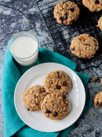 Three oatmeal breakfast cookies on a white plate next to a glass of milk.