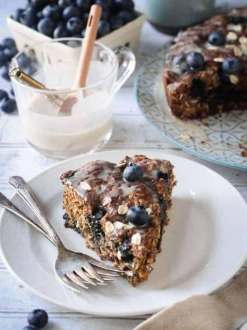 slice of blueberry cake on a plate with two forks in front of a cup of icing