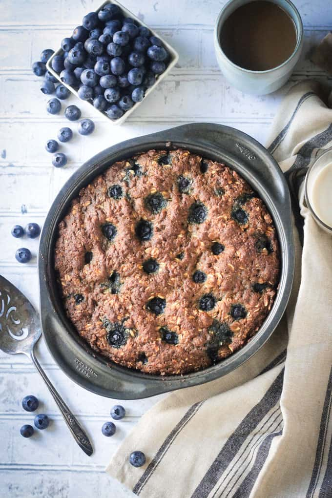 Overhead view of a breakfast cake dotted with blueberries in a round cake pan