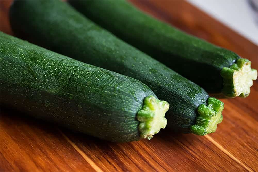 up close of three zucchini on a wooden cutting board
