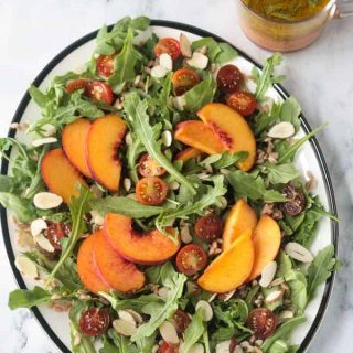 Platter of arugula salad topped with sliced peaches, halved grape tomatoes, slivered almonds, farro, and orange basil vinaigrette