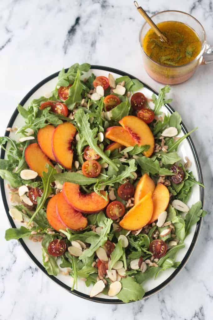 Platter of arugula salad topped with sliced peaches, halved grape tomatoes, slivered almonds, farro, and orange basil vinaigrette