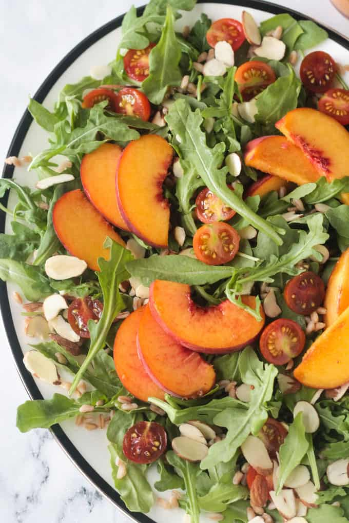 Close up overhead view of sliced peaches on an arugula salad