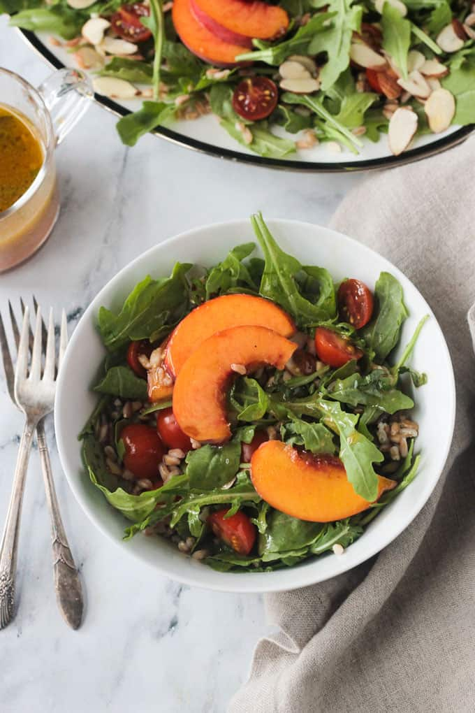 Arugula, peaches, and tomatoes in a white bowl